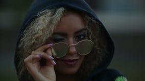 有卷曲看起来金发的行家女孩和被反映的太阳镜去和微笑 股票录像