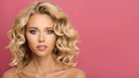 有卷曲美丽的头发的白肤金发的妇女 免版税库存照片