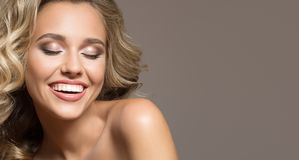 有卷曲美好头发微笑的白肤金发的妇女 免版税库存图片