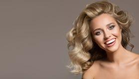 有卷曲美好头发微笑的白肤金发的妇女 免版税库存照片