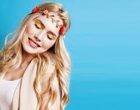 有卷曲金发和一点的年轻人相当白肤金发的女孩降低愉快微笑在蓝天背景,生活方式人 库存照片