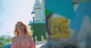 有卷曲金发和自然构成的愉快的迷人的女孩走沿晴朗的街道的 4k英尺长度 股票录像