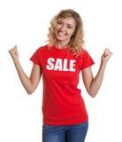 有卷曲金发和销售衬衣的惊人的妇女 免版税库存照片