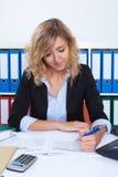有卷曲金发文字笔记的女实业家 免版税图库摄影