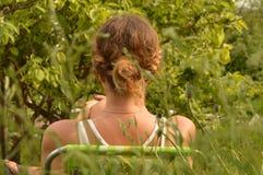 有卷曲金发的一个少妇在休息在一把椅子的一件白色T恤杉在庭院,垂直的射击里 库存图片