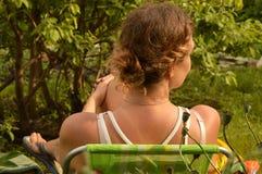 有卷曲金发的一个少妇在休息在一把椅子的一件白色T恤杉在庭院,垂直的射击里 库存照片