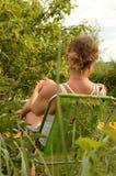 有卷曲金发的一个少妇在休息在一把椅子的一件白色T恤杉在庭院,垂直的射击里 免版税库存照片