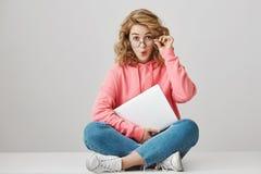 有卷曲金发的离开从惊奇的感兴趣的激动的年轻女学生室内射击玻璃,坐 免版税库存照片