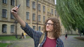 有卷曲长的头发的年轻英俊的人在采取与电话的在街道上的玻璃selfie和身分在学院附近或 股票视频