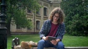 有卷曲长的头发的聪明的严肃的学生在玻璃拿着片剂和坐长凳在公园在学院或校园附近 影视素材