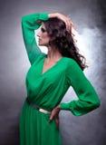 有卷曲长的头发的美丽的深色的妇女在绿色礼服 图库摄影