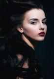 有卷曲飞行头发的秀丽年轻深色的妇女 免版税库存照片