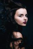 有卷曲飞行头发的秀丽年轻深色的妇女 免版税库存图片