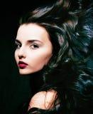 有卷曲飞行头发的,致命的femme秀丽年轻深色的妇女 库存照片