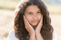 有卷曲黑发的青少年的女孩在自然 免版税图库摄影
