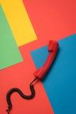 有卷曲绳子的红色电话机在明亮的背景 库存图片