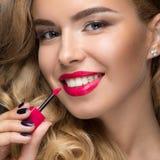 有卷毛、红色嘴唇和微笑的美丽的白肤金发的女孩在她的面孔 库存照片