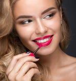 有卷毛、红色嘴唇和a的美丽的白肤金发的女孩 免版税图库摄影