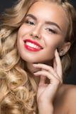 有卷毛、红色嘴唇和a的美丽的白肤金发的女孩 免版税库存照片