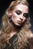 有卷毛和明亮的创造性的构成的女孩 在耳环和绿色上面的美好的模型 面孔的秀丽 免版税库存图片