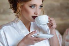有卷毛和红色嘴唇的一个女孩喝在一件丝绸晨衣的咖啡 女孩的特写镜头将采取a 库存照片