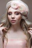 有卷毛的女孩在有面纱的一个帽子 与花花圈的美好的模型在她的头的 免版税图库摄影