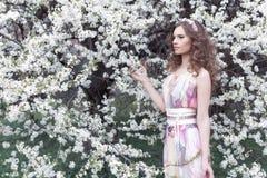 有卷毛的美丽的女孩在有一个花圈的空气色的礼服在她的走在公园的头在樱花附近 库存图片