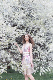 有卷毛的美丽的女孩在有一个花圈的空气色的礼服在她的走在公园的头在樱花附近 库存照片