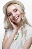 有卷毛的年轻微笑的女孩在帽子 在一件白色衬衣和别针花的一个美好的模型 库存图片