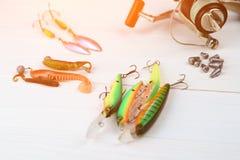 有卷轴、用作鱼饵的微曲金属片、滑车和晃摇物的钓鱼竿在抓或钓鱼的一条掠食性鱼箱子在白色葡萄酒木b 库存图片