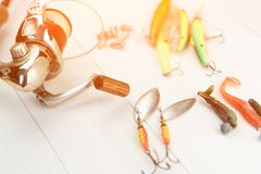 有卷轴、用作鱼饵的微曲金属片、滑车和晃摇物的钓鱼竿在抓或钓鱼的一条掠食性鱼箱子在白色葡萄酒木b 免版税图库摄影
