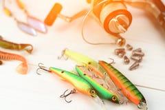 有卷轴、用作鱼饵的微曲金属片、滑车和晃摇物的钓鱼竿在抓或钓鱼的一条掠食性鱼箱子在白色葡萄酒木b 图库摄影