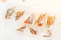 有卷轴、用作鱼饵的微曲金属片、滑车和晃摇物的钓鱼竿在抓或钓鱼的一条掠食性鱼箱子在白色葡萄酒木b 免版税库存照片