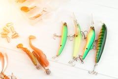 有卷轴、用作鱼饵的微曲金属片、滑车和晃摇物的钓鱼竿在抓或钓鱼的一条掠食性鱼箱子在白色葡萄酒木b 免版税库存图片