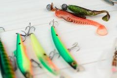 有卷轴、用作鱼饵的微曲金属片、滑车和晃摇物的钓鱼竿在抓或钓鱼的一条掠食性鱼箱子在白色葡萄酒木b 库存照片