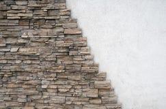有压印的砖的自然石墙,划分倾斜地与白色墙壁 免版税库存照片