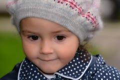 戴有厚颜无耻的微笑的女孩温暖的羊毛帽子 库存图片