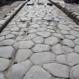 有原始的车轮痕迹的古老路在石头,庞贝城 免版税库存图片