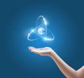 有原子图象的手在蓝色背景 免版税库存图片