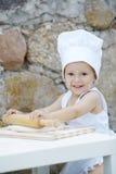 有厨师帽子烹调的小男孩 免版税库存图片