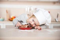 有厨师帽子的小滑稽的女孩吃蛋糕的 免版税库存照片