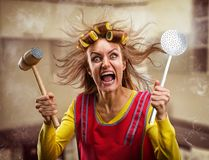 有厨房工具的疯狂的主妇 免版税库存照片