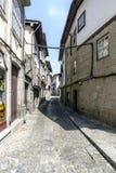有参差不齐的鹅卵石地板的狭窄的偏僻的胡同和有石门面的哥特式样式房子在一个村庄在葡萄牙叫Guima 库存图片