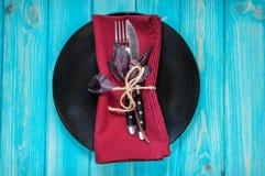 有叉子、刀子、餐巾和蓬蒿的黑色的盘子在蓝色木桌上 免版税库存图片