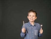 有叉子和刀子的小男孩。饥饿的孩子。 免版税库存照片