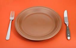 有叉子和刀子的布朗陶瓷板材在红色设置了 免版税库存照片