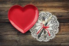 有叉子和刀子的空的红色心形的板材 免版税库存照片