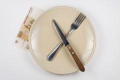 有叉子和刀子的,关闭空的板材是一百卢布笔记,白色背景 库存照片