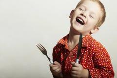 有叉子和刀子的滑稽的矮小的英俊的男孩 库存图片