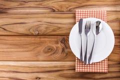 有叉子的白色空的在木桌上的板材和匙子 库存照片